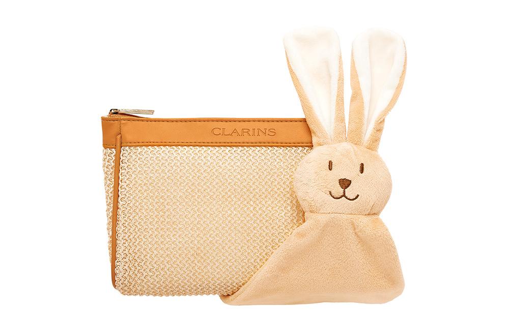 Trousse de soins maternité et lapin en peluche Clarins Photographie packshot d'une trousse et d'un jouet en peluche Clarin