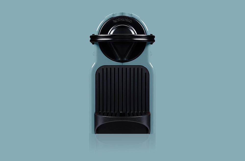 Photographie packshot en studio d'une machine à café Nespresso.Vue de face sur fond bleu.