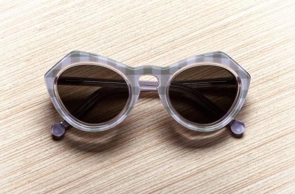 Prise de vue packshot publicitaire d'une paire de lunettes solaires Carven présentée sur un fond en bois.